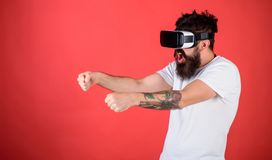 Virtual racing concept. Man with beard in VR glasses driving car, red background. Guy play racing game in VR. Hipster on stock photo