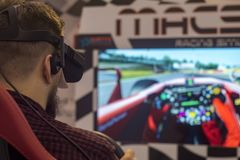 Virtual racing simulator. Man play the video game with virtual reality device in this context, virtual reality concerns a racing car race. photo taken at enada stock photos