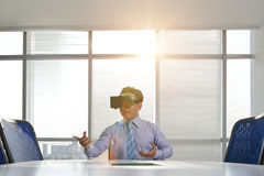 Virtual reality business. Businessman in virtual reality goggles holding business meeting in the office stock image