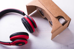 Virtual reality cardboard headset and red headphone over white Royalty Free Stock Photo