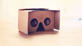 Virtual reality cardboard headset. On a table in natural light Stock Photos