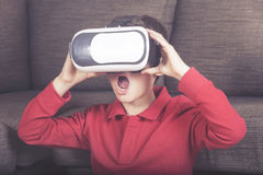 Virtual reality cncept. Excited little boy reacts while experiencing virtual reality at home royalty free stock images