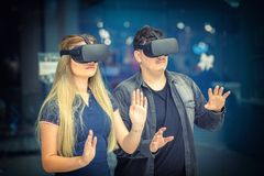 Virtual reality concept with young woman and man having fun with headset goggles during VR experience royalty free stock photos