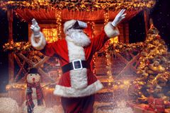 In virtual reality. Cool modern Santa Claus in virtual reality glasses standing near his decorated house. Computer games. Christmas and New Year concept royalty free stock image