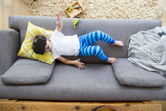 Virtual Reality Dinosaurs. View from above of a little boy lying on his sofa with a box of dinosaurs. He is wearing a virtual reality headset and has his arms stock images