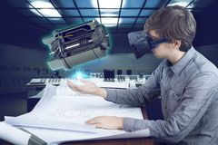 Engineer / architect workplace. Virtual reality in engineering concept. Male / man engineer wearing shirt and vr glasses working with holographic engine for Stock Images