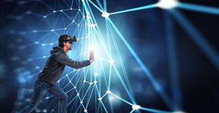 Virtual reality experience. Man in VR glasses. Young man in VR glasses pushing a block chain network hologram stock photo
