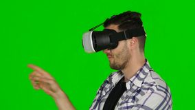 Virtual reality game. Girl with pleasure uses head-mounted display. Green scree. Close up. Virtual reality game, girl with pleasure uses head-mounted display stock video footage
