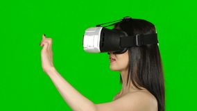 Virtual reality game. Girl with surprise and pleasure uses head-mounted display. Green screen. Close up. Virtual reality game, girl with surprise and pleasure stock footage