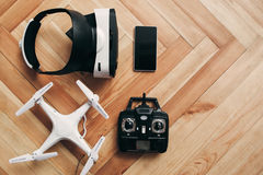 Virtual reality glasses and drone, free space. Flat lay. Top view on quadrocopter with remote control and vr headset with smartphone on wooden background, copy Royalty Free Stock Photography