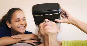 Virtual Reality Happy Grandmother And Young Girl Playing Togethe. Family relationship between grandmother and granddaughter. Happy old women playing virtual Stock Image