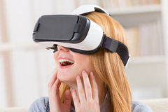 Virtual reality headset. Happy woman using virtual reality headset at home stock photos