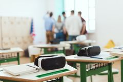 Virtual reality headsets on tables with teacher and high school students standing behind. In classroom royalty free stock image