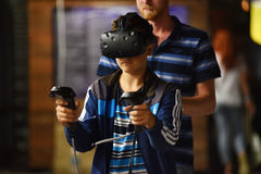 Virtual reality HTC Vive headset and hand controls. CLUJ-NAPOCA, ROMANIA - AUGUST 5, 2016: Boy tries virtual reality HTC Vive headset and hand controls during Stock Image