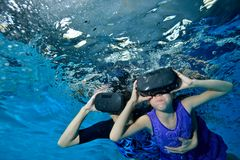 Virtual reality. A little girl with her mother in a virtual reality helmet on her head floats from the bottom to the surface under. Water. Bottom view stock images