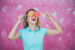 Virtual reality with lollipops. Pretty girl with candies like su. N glasses. Pink background, holiday concept Royalty Free Stock Photo