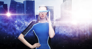 Woman in virtual reality glasses over space city Stock Photos