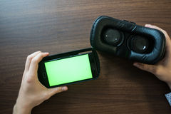 Virtual reality, VR, helmet and smartphone with green screen for key chroma screen. Virtual reality, VR, helmet and smartphone with green screen for key Royalty Free Stock Photo