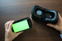 Virtual reality, VR, helmet and smartphone with green screen for key chroma screen. Virtual reality, VR, helmet and smartphone with green screen for key Royalty Free Stock Image