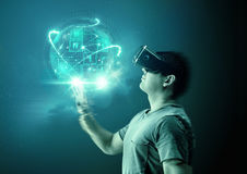 Virtual Reality Worlds. A young man wearing virtual reality & x28;VR& x29; goggles and headset with a projection of a digital world stock image