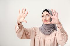 Muslim woman pointing on virtual screen, copy space. Virtual sceen technology. Eastern woman in hijab working on ivisible digital tablet, copy space, selective Royalty Free Stock Images