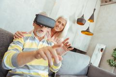 Retired aged man trying up VR glasses. Virtual touch. Close up of a retired men sitting on the sofa and trying up VR glasses while his wife standing behind Stock Photo
