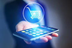 Virtual trolley going out of a smartphone - shopping online conc Royalty Free Stock Photography