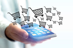 Virtual trolley going out of a smartphone - shopping online conc Stock Photography