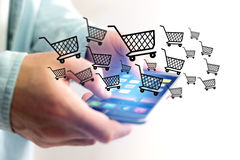 Virtual trolley going out of a smartphone - shopping online conc Stock Image