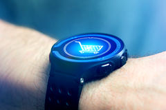 Virtual trolley going out of a smartwatch - shopping online conc Stock Photography