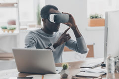 Virtual work. Handsome young African man in VR headset pointing in the air while sitting at the desk in creative office Royalty Free Stock Images