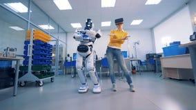 Virtueel Werkelijkheidsconcept Het wijfje in VR-glazen maakt het dansen bewegingen en een robot kopieert hen stock videobeelden