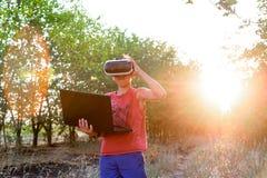 Virtuele die spelen op werkelijkheid worden gebaseerd Een jongen op aard in virtuele ruimte, VR-glazen, een bos, laptop stock fotografie