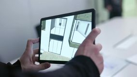 Virtuele tekening van huis op tablet voorraad De tablet van de zakenmanholding met virtueel werkelijkheidsproject thuis in bestuu stock footage