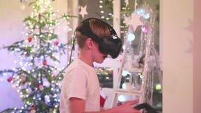 Virtuele werkelijkheidsglazen Een tiener die een computerspel met een helm spelen stock video