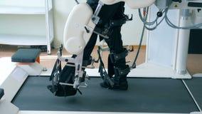 Virtuele werkelijkheidssimulator voor patiënt rehab Zijaanzicht van een gehandicapte mens die zijn benen op een het lopen spoor o stock videobeelden
