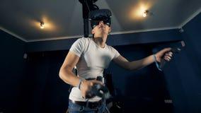 Virtuell verklighet som spelar begrepp Ung man i mitt av att spela process med ett virtuell verklighetsystem stock video