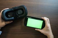 Virtuell verklighet, VR, hjälm och smartphone med den gröna skärmen för arkivfoto