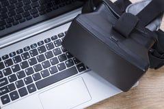 virtuell verklighethörlurar med mikrofon för 3d VR på en bärbar dator Royaltyfri Fotografi
