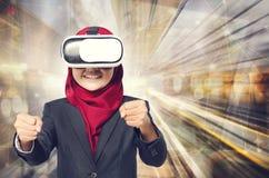 Virtuell verklighethörlurar med mikrofon och handling för yrkesmässig ung muslimah bärande som körning över abstrakt bakgrund för Arkivbild