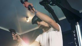 Virtuell verklighethörlurar med mikrofon som spelar lek 360 Virtuell verklighetsystemet används av en man som flyttar hans händer arkivfilmer