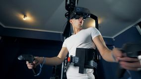 Virtuell verklighetplattform och en ung man som använder den i en spela process Virtuell verklighet som spelar begrepp arkivfilmer