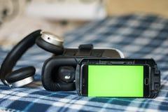 Virtuelle Realität, Sturzhelm und Smartphone mit grünem Schirm für stockbild