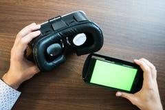 Virtuelle Realität, VR, Sturzhelm und Smartphone mit grünem Schirm für lizenzfreie stockfotos