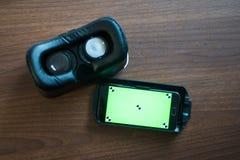 Virtuelle Realität, VR, Sturzhelm und Smartphone mit grünem Schirm für stockfoto
