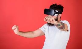 Virtuelles laufendes Konzept Mann mit Bart in VR-Gläsern, die Motorrad, roten Hintergrund fahren Hippie auf überzeugtem Gesicht Stockbild