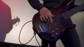 The musician plays bass guitar. Close-up. Virtuoso guitar playing. Hands close-up. Room with concert light