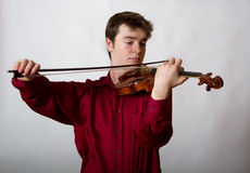 Virtuoso Teen Male Violinist in red. Shirt playing Royalty Free Stock Image