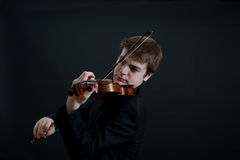 Virtuoso Violinist Playing. Virtuoso Teen Male Violinist on Dark Background Stock Photo