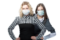 Viruses. Two young caucasian girlfriends standing in medical masks looking appear isolated over white background Stock Photography